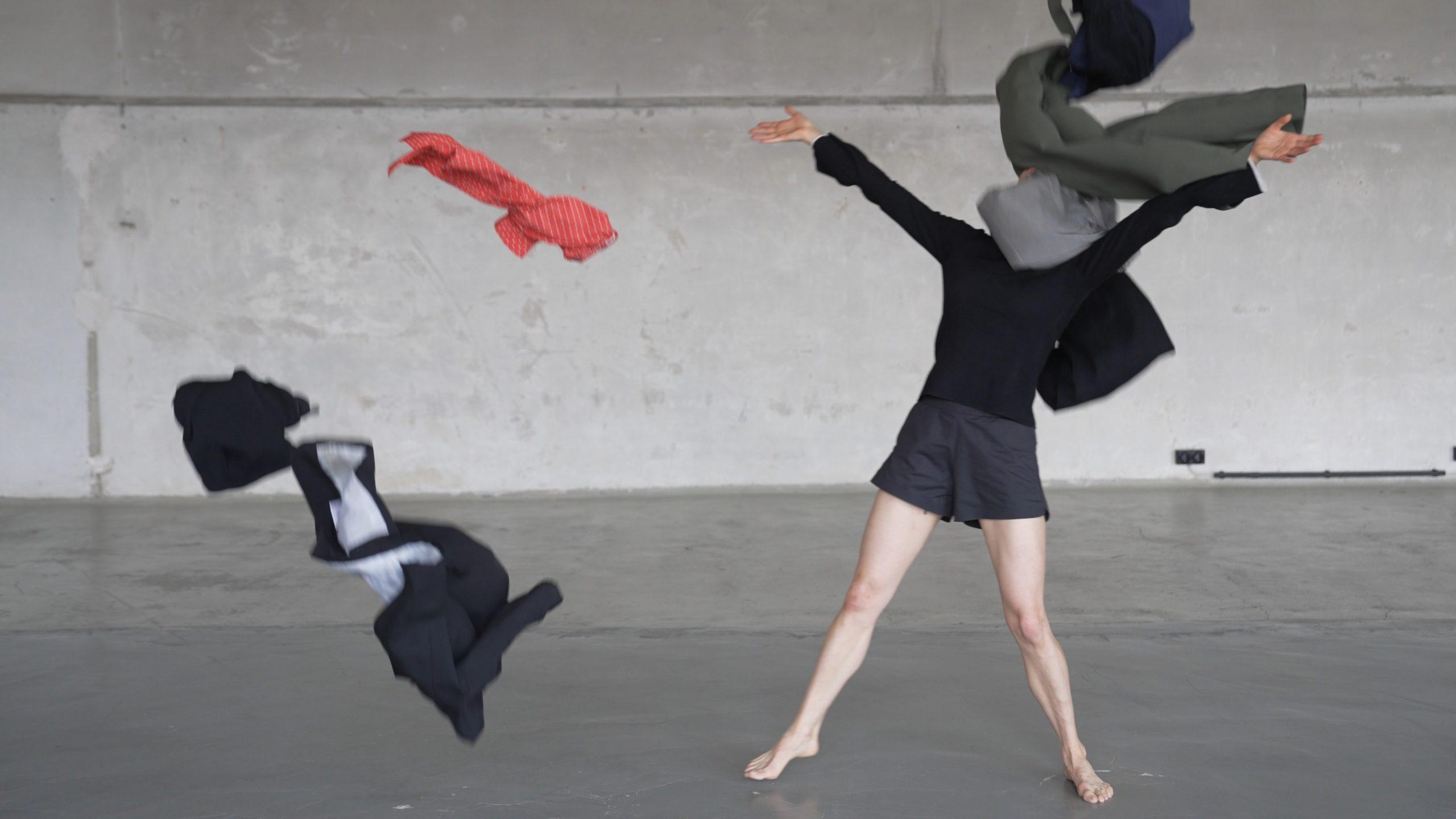 Tanz vom Tod | Das letzte Plötzlich | Maria Walser © Nora Wetzel. Eine Frau in einem schwarzen kurzen Kleid mit nackten Beinen steht breitbeinig auf der Bühne. Ihr Kopf ist von einem grauen Stoff verdeckt und zwei Kleidungsstücke fliegen durch die Luft.